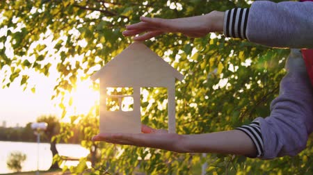 miniatűr : Close-up shot of female hands holding model of wooden house through window of which setting sun is visible on background of green leaves by sea.
