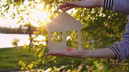 miniatűr : Close-up shot of female hands holding model of wooden house through window of which setting sun is visible on background of green leaves by river.