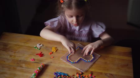 boncuklar : Handheld shot of little cute caucasian girl makes colorful decoration in shape of heart from mosaic. Child sits at wooden table and prepares gift for day of mother, father or valentine. Stok Video