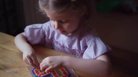 puzle : Child sits at wooden table and makes gift.Tracking shot behind little cute caucasian girl makes colorful decoration in shape of heart from mosaic.