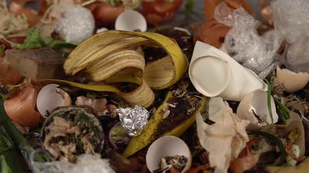 rothadás : Tracking shot close up of food debris mixed with inorganic waste. Landfill with unsorted garbage,problems of waste disposal from human activities.