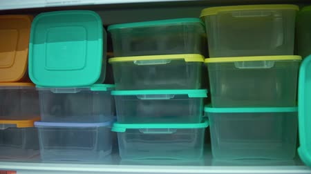 comparer : Point of view on shelf with colorful reusable food containers in supermarket.Camera moves along the rack with lunch boxes, close-up.