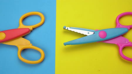 řezačka : Close-up of a variety of wavy blade scissors for scrapbooking on colorful paper moves from left to right. Abstract minimal background. Dostupné videozáznamy