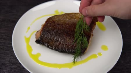 seafood dishes : Hand of cook puts dill on dish around pink salmon. Closeup of a piece of red fish fried to a golden crust lies on a white plate.