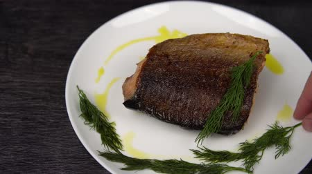 kapor : Closeup of a piece of red fish fried to a golden crust lies on a white plate. Hand of cook puts dill on part of roasted salmon. Stock mozgókép