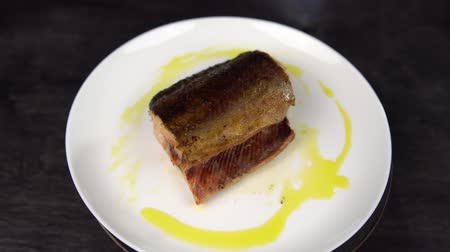 seafood recipe : Close-up of piece of red fish fried to golden crust on white plate rotates against black table. Stock Footage