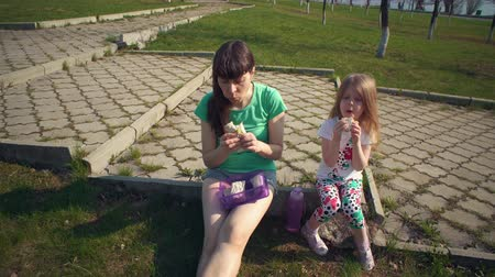 a small bottle : Mother and cute daughter eat shawarma together, young brunette woman and little blonde girl are sitting on curb of park path on warm day.