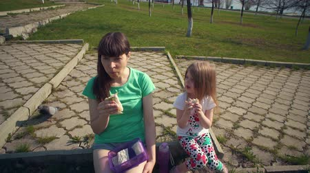 shoarma : Mother and cute daughter eat shawarma together, young brunette woman and little blonde girl are sitting on curb of park path on warm day.