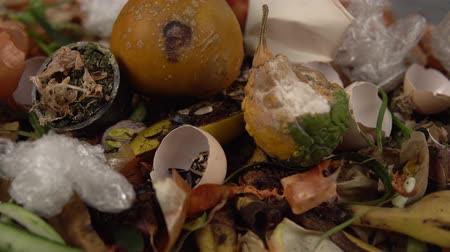 biodegradable : Tracking shot close up of food debris mixed with inorganic waste. Landfill with unsorted garbage,problems of waste disposal from human activities.