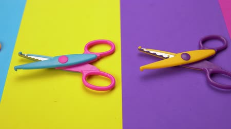 scrapbook : Set of a variety of wavy blade scissors for scrapbooking on colorful paper moves from right to left. Abstract minimal background with space for text. Stock Footage
