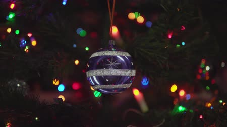 lâmpada elétrica : Glass blue Christmas ball with snowflakes and stripe rotated on branch on blinking garland background. Xmas and New Year Decoration. Stock Footage