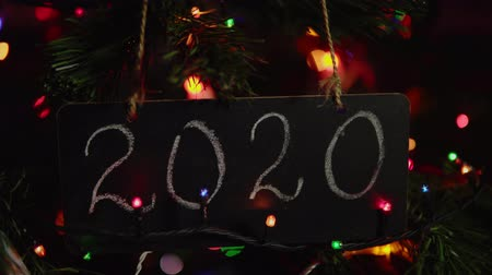 yirmi : Close up of black letter board with number 2020 title on it hanging on branch Christmas tree among multicolor round bokeh in background, camera moves from right to left. Happy New Year greeting card.