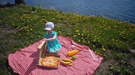 sea piece : Little cute blonde girl opens cardboard box with pizza. Child sits on checkered blanket next to dandelions on seacoast. Stock Footage
