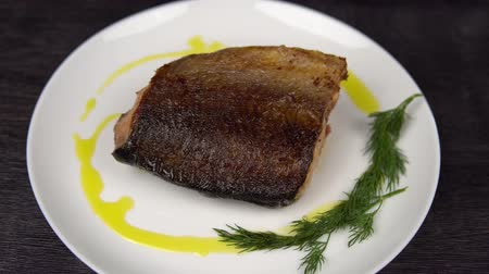 kapor : Hand of cook puts dill on dish around salmon, trekking shot. Closeup of a piece of red fish fried to a golden crust lies on a white plate.