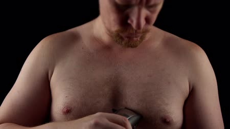 navalha : Young caucasian man shaves his chest on black background.