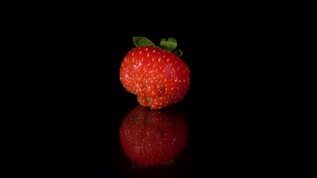 výřez : Close-up of one red ripe strawberry turns around itself on mirror surface, seamless loop. Fresh juicy berry isolated on black background.