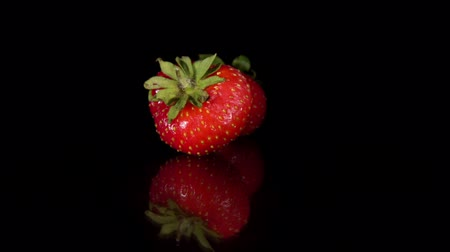 yaprak döken : Close-up of two red ripe strawberries are turning around on a mirror surface, seamless loops. Fresh juicy berries isolated on a black background. Stok Video