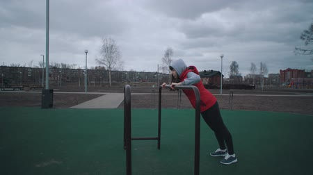 flexibilidade : Young sports woman in red jacket sleeveless makes warm-up on sport ground in public park on cloudy morning.Concept of healthy lifestyle.
