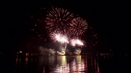 yansıyan : Powerful sparks of festive firecracker illuminate the sky above surface of dark river. Colored lights fireworks are reflected in water on celebration.