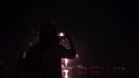 brotos : Silhouette of a girl with a smartphone on the background of bright colorful fireworks in the black sky.