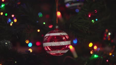 adwent : Glass red Christmas ball with snowflakes and stripe rotated on branch on blinking garland background. Xmas and New Year Decoration.Camera moves away from spinning toy.