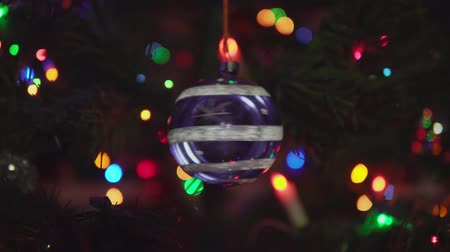 adwent : Glass blue Christmas ball with snowflakes and stripe rotated on branch on blinking garland background. Xmas and New Year Decoration.Camera is approaching spinning toy. Wideo