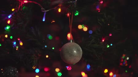 bombki : Beautiful golden Christmas tree ball rotated on branch on blinking garland background. Xmas and New Year Decoration.