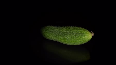 yansıyan : Fresh gherkin rotates on a black background, one small green-skinned cucumber is reflected in a dark mirror surface, natural vegetables organic food, seamless loops. Stok Video