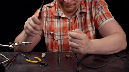 biztosíték : Process of replacing cable for audio cinch connector.Muscled blond electrician solder strip the wire from braid for subsequent soldering to male RCA jack plug.