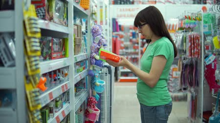 section : Young brunette woman chooses colored plastic container with lid for needlework in department of household goods supermarket.