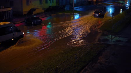 pozzanghera : Cars gently drive along flooded one-way road after storm. Storm sewage can not cope with huge stream of water after heavy rain.