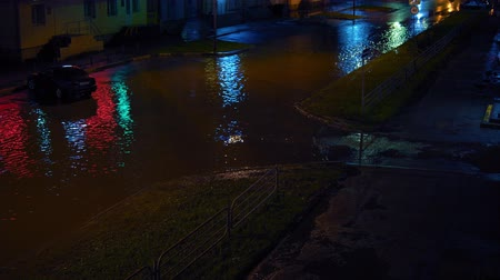pozzanghera : Cars try to drive on flooded one-way road at night.Storm sewage can not cope with huge stream of water after heavy rain. Neon light from the signage is reflected in huge puddle.