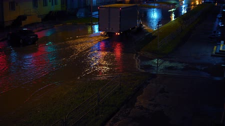 yansıyan : Small truck is moving slowly along a flooded one-way road. Storm sewage can not cope with huge rainfall after heavy rain. Neon lights from signage are reflected in muddy water.