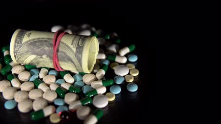addiction recovery : Bundle of hundred-dollar bills, rolled up into pipe and pulled by red rubber band, lies on pile of drugs. White tablets, white-green capsules, blue pills reflect off mirror surface. Stock Footage