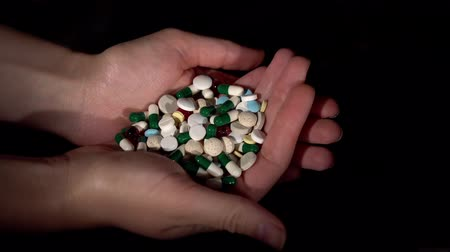 aşırı doz : Top view close-up of someones hands holding huge pile of multi-colored pills and capsules on black background.