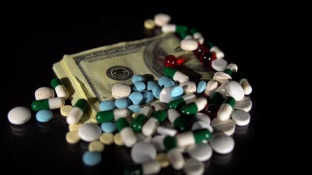 medicament : Bunch of different medicines on hundred dollar bills rotate on black background. Capsules and tablets exceed allowable dose of medication, addiction problems, incurable diseases or mental disorders.
