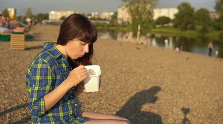 kluski : Young brunette woman eats instant noodles from white box using chopsticks, girl in blue checkered shirt sits on wooden deck chair on pebble beach