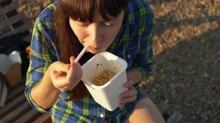 kluski : Top view on young brunette woman eats instant noodles from white box using chopsticks, girl in blue checkered shirt sits on wooden deck chair on pebble beach