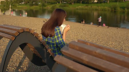 kluski : Handheld shot on back of young brunette woman eats instant noodles from white box using chopsticks, girl in blue checkered shirt sits on wooden deck chair on pebble beach