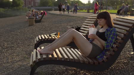 kluski : Girl eats instant noodles from white box using chopsticks, brunette in blue checkered shirt and beige shorts barefoot sits on wooden deck chair on pebble beach, against blurred people, handheld shot Wideo