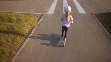 two wheeled : Back view blond little girl rides a childrens two-wheeled scooter on bicycle path in city park during afternoon at sunset.Happy kid enjoys walk.
