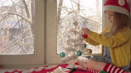 bombki : Little cute blond girl in red Santa Claus hat decorates white shiny Christmas tree with small balls.Child sits on striped red-white plaid on windowsill, outside tree branchs is covered with snow. Wideo