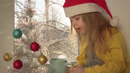 bombki : Little blonde girl in red Santa Claus hat blows hot cocoa in blue mug.Child sits on windowsill next to white artificial year tree decorated with colored balls, outside on branches of snow, dolly shot. Wideo