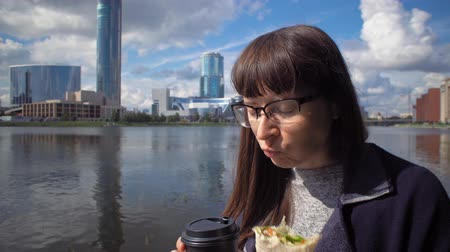 pita : Happy businesswoman in glasses eats doner kebab and drinks coffee for lunch while walks along the riverbank in downtown.