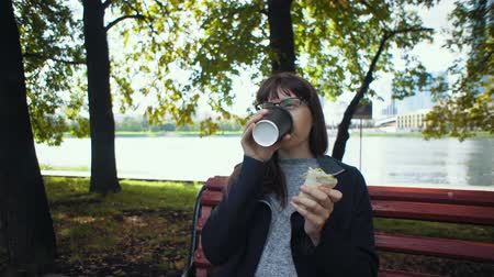 shoarma : Brunette young woman eats doner kebab and drinks coffee for lunch. Happy businesswoman in glasses sit on wooden bench under trees near riverside in downtown.