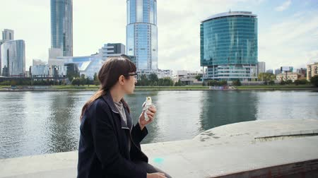 жевание : Happy businesswoman sitting on concrete fence near riverside in downtown. Girl in glasses eats doner kebab for lunch.