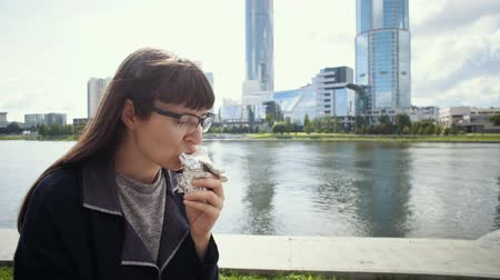 pan pita : Happy businesswoman sitting on concrete fence near riverbank in downtown.Girl in glasses eats doner kebab for lunch. Archivo de Video