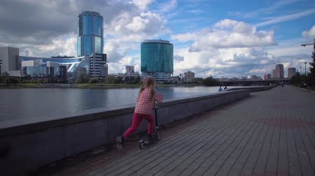 two wheeled : Little cute blonde girl riding two-wheeled scooter along riverside in downtown. Stock Footage