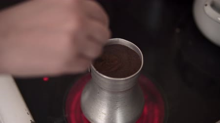 alumínium : Close-up top view of female hand with spoon stirs hot aromatic americano in an aluminum cezve, process of brewing ground coffee beans on an electric stove at home.