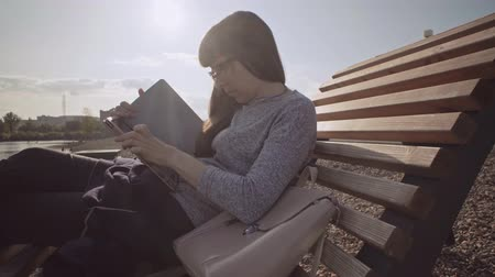 use laptop : Young woman in glasses uses tablet while sitting on wooden deck chair on pebble beach in cool sunny day.